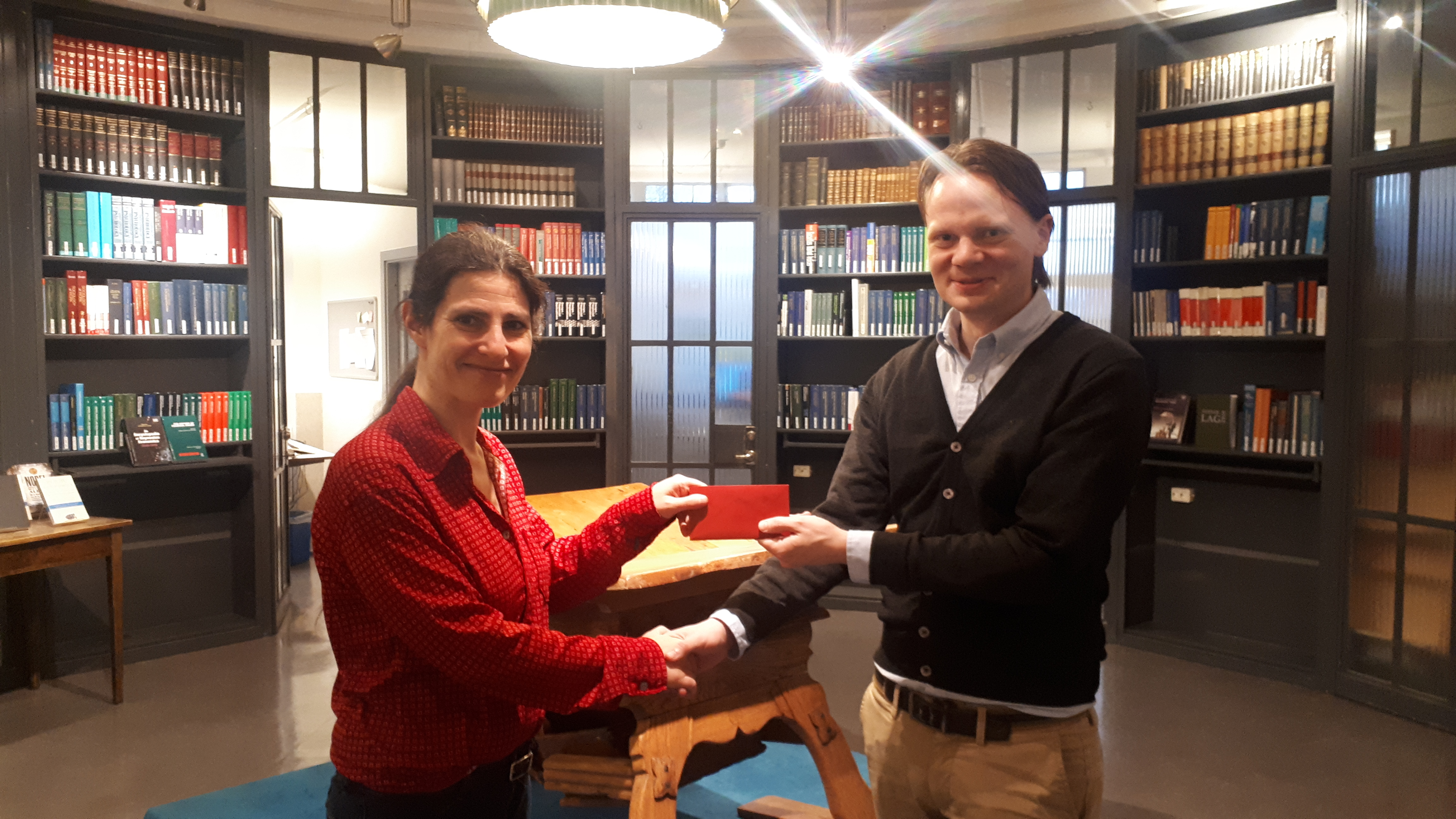 Gabriel is handed the prize by Library Manager Miriam Nauri