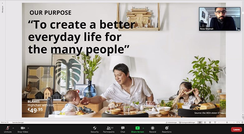 PPT zoom clip with presenter in a small picture in a slide covering a family where the father feeding his child in a IKEA furnished kitchen.