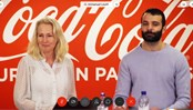 Two representatives from Coca Cola European partners, a male and female, holding a videomeeting both looking into the camara. In the background the company logo.