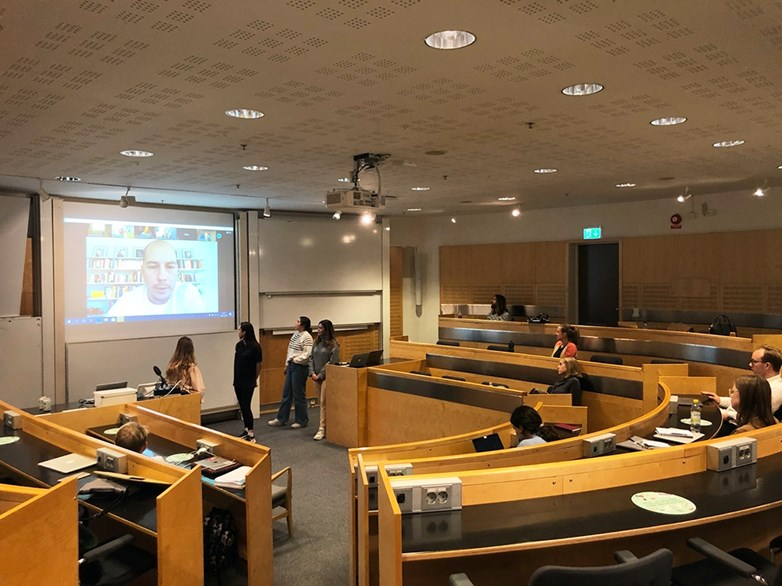 Students looking at a video broadcast with Axel Johnson in a lecture room